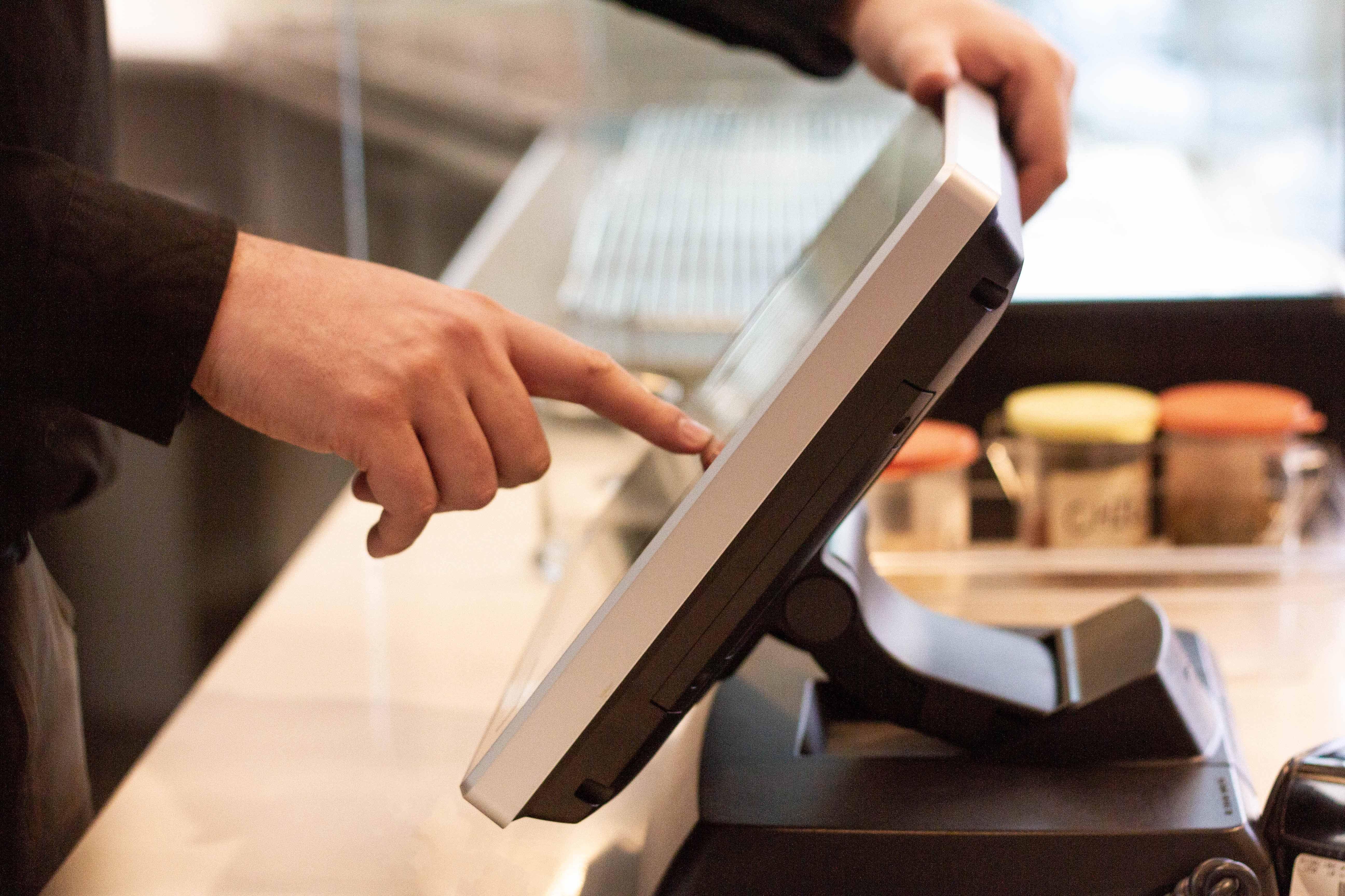 Pizzeria employee using a touchscreen POS display