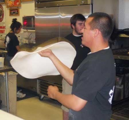 Pizza Factory employee tossing dough