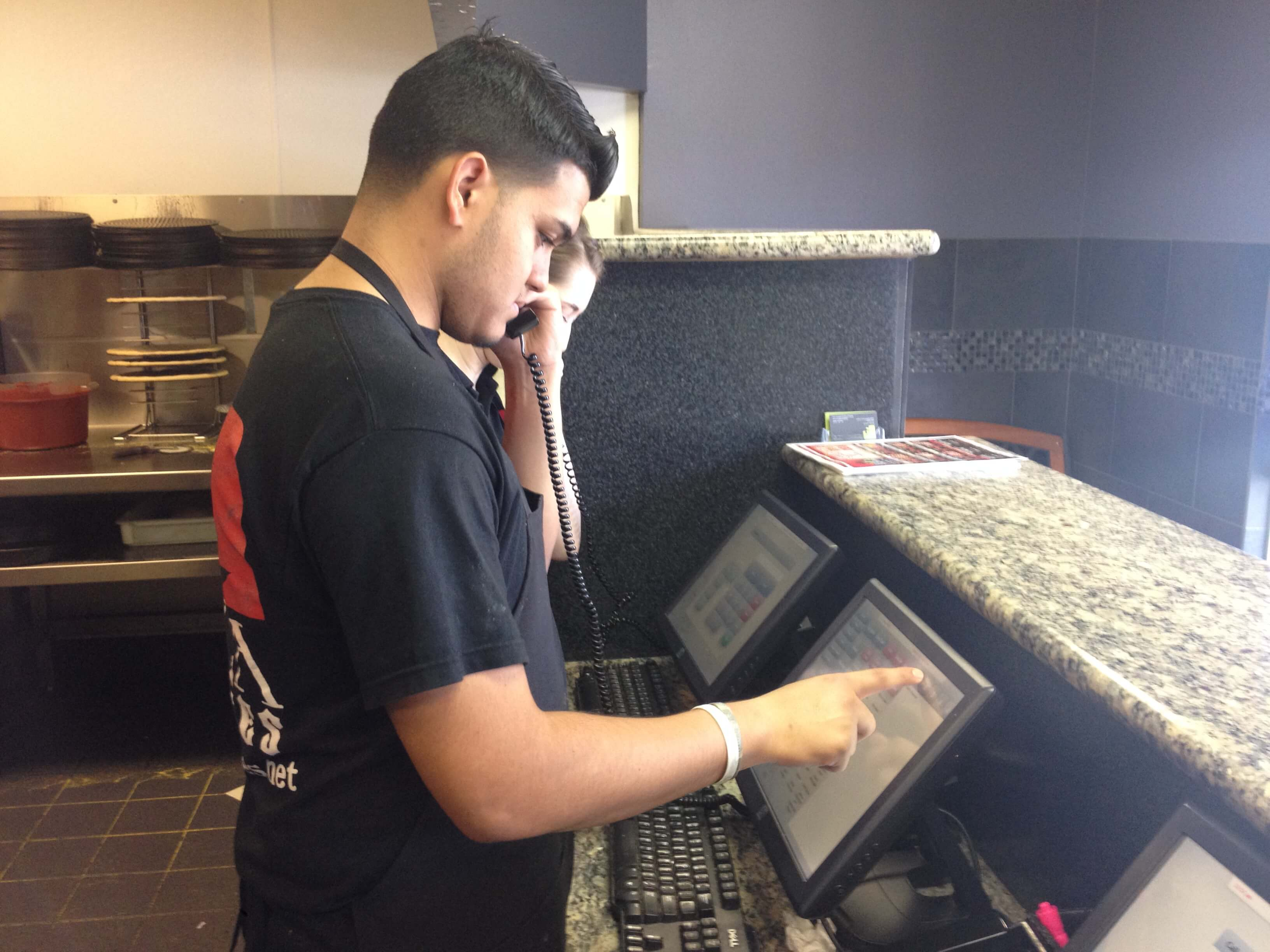A Pizza Pirate employee entering a phone ordering into the POS