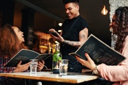 A waiter taking an order on a tablet